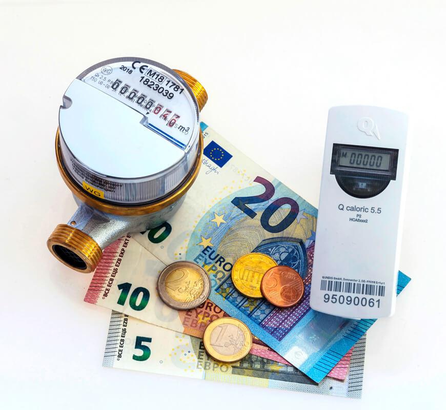 Wasser- und Wärmezähler liegen auf Bargeld